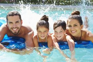 Photograph Of Family On Airbed In Swimming Pool