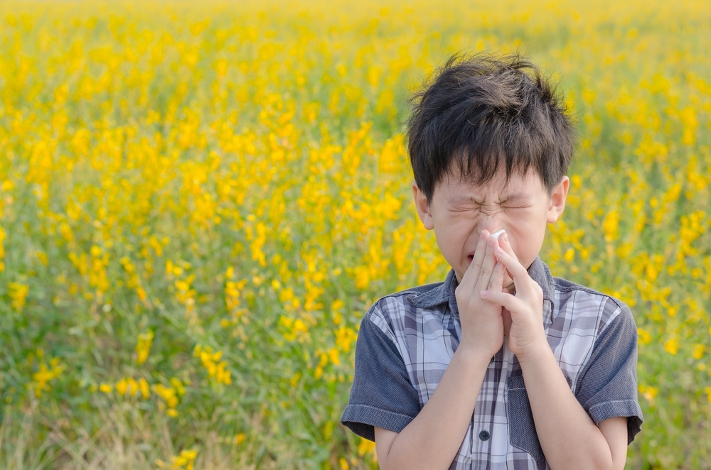 young boy blowing his nose in a field with flowers because he has las vegas allergies
