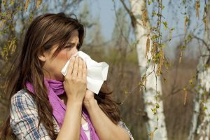 A photograph of a woman suffering from allergies blowing her nose, with trees in the background.