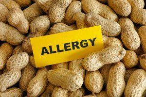 """A pile of peanuts with a card with the word """"allergy"""" on it, on the top of the pile"""