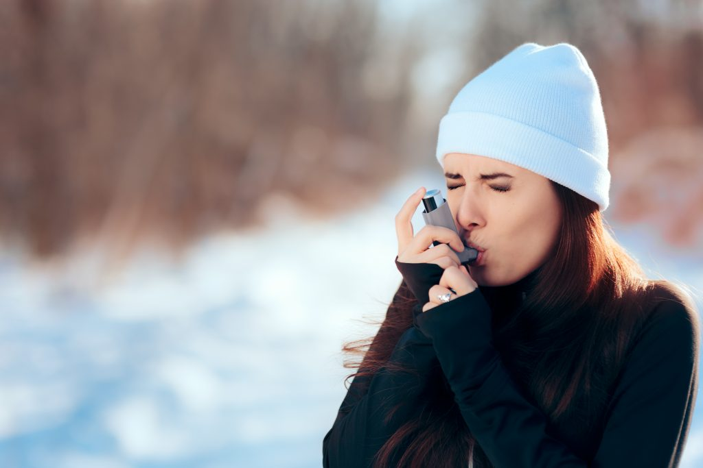 woman using inhaler outside during winter due to las vegas allergies