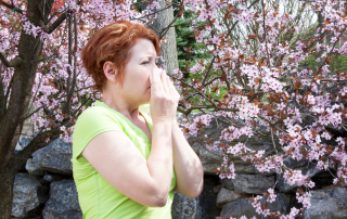 woman blowing her nose in front of blooming flowers because of Las Vegas allergies